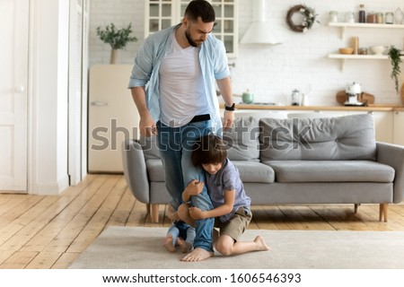 Photo of  Irritated father leaving while his children keep him not letting go. Mom dad separation, kids passing through parents divorce, alimony, another family, cheater, psychological effects of split concept