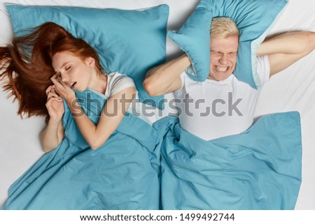 irritated frustrated man covering his ears with a pillow. he has terrible,scary dream. top view photo. affected sleep