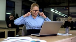 Irritated lady closing ears with fingers, noisy colleagues distracting from work
