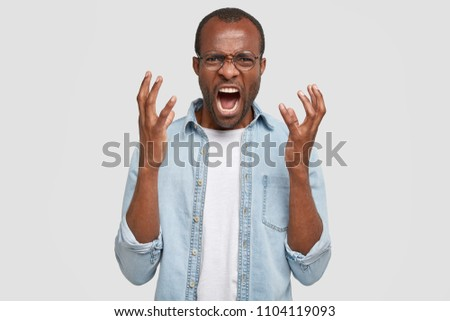 Irritated young African American guy gestures angrily, exclaims loudly and has furious expression, being annoyed after quarrel with colleagues, poses against white background. Anger concept. #1104119093
