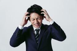Irritated young asian businessman. Facial expression.