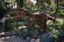Irritator- Early Cretaceous, 110 million years ago. In the Dinopark. Dinosaur statue in the forest park in nature for background. Realistic model of hungry big Irritator. Dinopark in Turkey, Goynuk.
