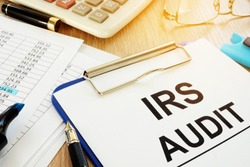 IRS audit documents with clipboard on a desk.