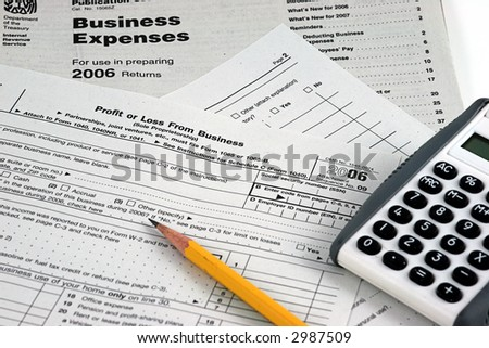 IRS Business Tax forms with pencil and calculator