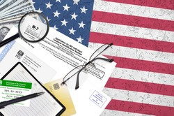 IRS form W-7 Application for IRS individual taxpayer identification number lies on flat lay office table and ready to fill. U.S. Internal revenue services paperwork concept