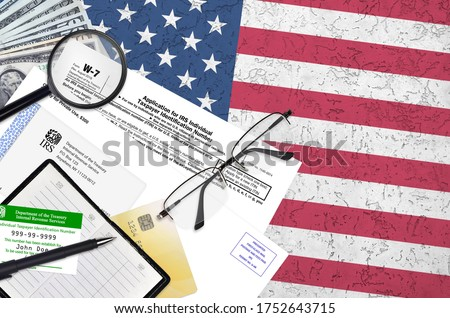 IRS form W-7 Application for IRS individual taxpayer identification number lies on flat lay office table and ready to fill. U.S. Internal revenue services paperwork concept Stock photo ©