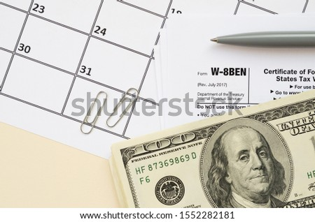 IRS Form W-8BEN Certificate of foreign status of beneficial owner for United States tax withholding and reporting for individuals blank lies with pen and hundred dollar bills on calendar page #1552282181