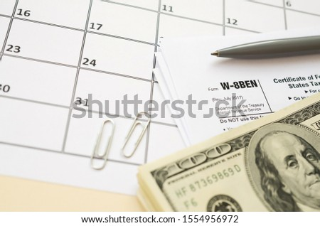 IRS Form W-8BEN Certificate of foreign status of beneficial owner for United States tax withholding and reporting for individuals blank lies with pen and hundred dollar bills on calendar page #1554956972