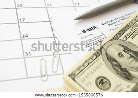 IRS Form W-8BEN Certificate of foreign status of beneficial owner for United States tax withholding and reporting for individuals blank lies with pen and hundred dollar bills on calendar page #1555808576