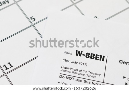 IRS Form W-8BEN Certificate of foreign status of beneficial owner for United States tax withholding and reporting for individuals blank lies on empty calendar page