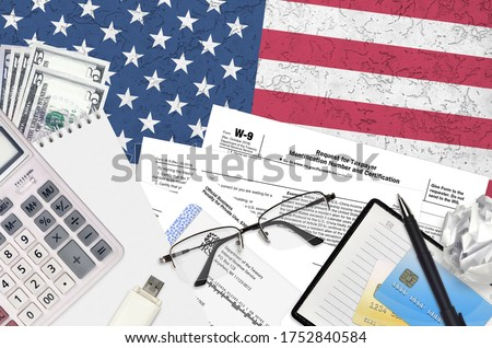IRS form W-9 Request for taxpayer identification number and certification lies on flat lay office table and ready to fill. U.S. Internal revenue services paperwork concept. Time to pay taxes Stock photo ©
