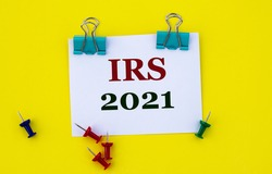 IRS (Internal Revenue Service) 2021 - acronym on white paper with clips on yellow background with buttons and pencil. Business concept