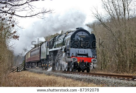 IRWELL, ENGLAND - JANUARY 22: Preserved steam locomotive 'Duke Of Gloucester 'passes at speed through the Irwell Valley during the East Lancs Railway winter steam gala on January 22, 2011 in Irwell, England.