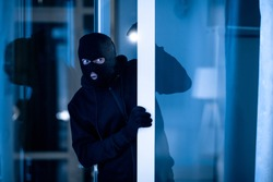 Is Anybody Home. Cautious masked thief looking and peeping into office through window or glass door with torch flashlight