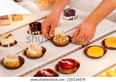 Is this your choice? Close-up of male hand taking a cupcake from showcase while standing in bakery shop