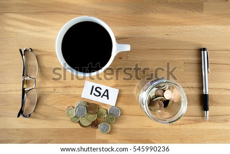 ISA words on desk with coins and pen