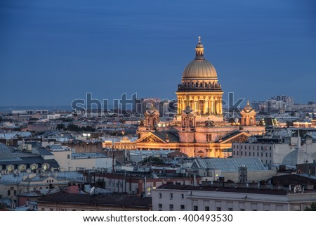 Isaac Cathedral among roofs of buildings, St Petersburg, Russia at night