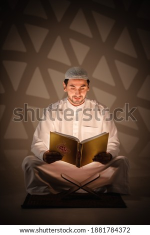 islam religion background of muslim man holding holy al quran book reading and study al quran book with written arabic calligraphy meaning of Al Quranin dark room Stok fotoğraf ©