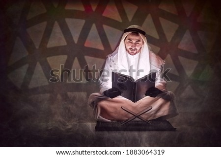 islamic background of arabic muslim man holding holy al quran book reading and study al quran book with written arabic calligraphy meaning of Al Quranin in dark room in warm tone Stok fotoğraf ©