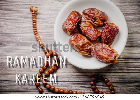 """Islamic concept for Ramadhan, the fasting month with """"Ramadhan Kareem"""" wordings and the  Tasbih (rosary beads) and Tamar (Dates)  against wooden background #1366796549"""