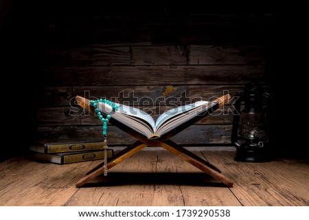 Islamic concept - The Holy Al Quran with written Arabic calligraphy meaning of Al Quran and rosary beads or tasbih, Arabic word translation : The Holy Al Quran (holy book of Muslim)