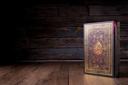 Islamic concept - The Holy Al Quran with written Arabic calligraphy meaning of Al Quran, Arabic word translation : The Holy Al Quran (holy book of Muslim), on black background, with copy space.