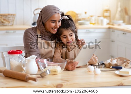 Islamic Lady Baking With Her Little Daughter In Kitchen, Using Digital Tablet For Checking Cookies Recipe Online, Happy Muslim Mom And Her Child Enjoying Homemade Pastry, Having Fun Together At Home