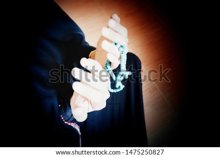 Islamic women is praying and requesting blessings from the god in the hands of a rosary to count the number of praise.