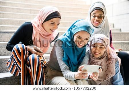 Islamic women sharing smartphone