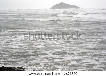 Island barely visible through the waves and gusts of an ocean storm on the pacific