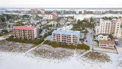 Island Clearwater Beach FL. Beach on Gulf of Mexico. Spring break or Summer vacations in Florida. Hotels, restaurants and Resorts. United States of America. Aerial view of city.