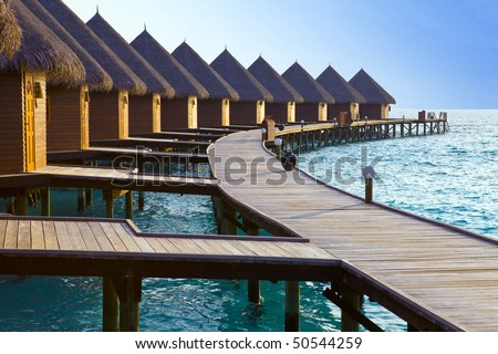 Island in ocean, Maldives Maldives.  Villa on piles on water at the time sunset.