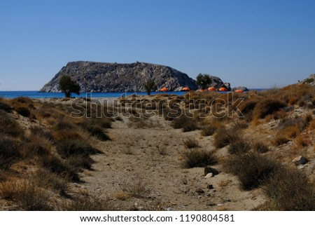 Island of Syros in greece, panorama of  cliff close to Varvarousa beach with sand land and sea. Dry land with umbrellas on the background. #1190804581