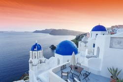 Island Santorini  in Greece. Beautiful sunset scenery with traditional Greek white architecture. Oia village and blue domed famous church.