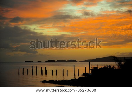 Island Sunset with orange glow silhouette of the land and poles lined up on the water edge and thick bright clouds over the sea at the end of the day in Cocorite Trinidad Caribbean