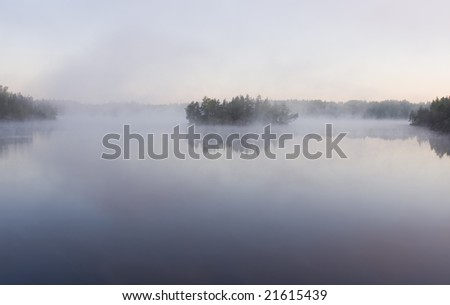 Islands in morning fog on wild forest lake in Karelia