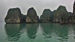 Islands with bizarre outlines hide in the fog. Green vegetation on the steep slopes. Reflection on the water. Halong Bay. Vietnam
