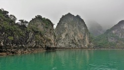 Islands with steep slopes and green vegetation hide in the fog. The emerald water of Halong Bay is calm. Vietnam
