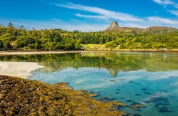 Isle of Eigg, Small Isles, Hebrides, Scotland.  A beautiful bay at low tide with silver sands and An Sgurr in the background, also reflected in the clear blue waters. Horizontal, space for copy