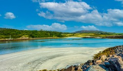 Isle of Eigg, Small Isles, Hebrides, Scotland.  A beautiful bay at low tide with silver sands, blue sea, blue sky and white fluffy clouds. Landscape, Horizontal, space for copy.