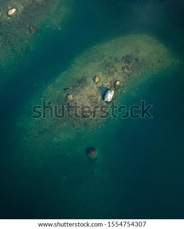 Islet with shallow bottom surrounding at blue clear-watered lake. Aerial shot. #1554754307