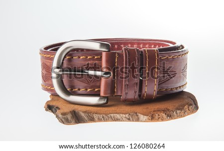 Isolate of leather belt on piece of wood against white background