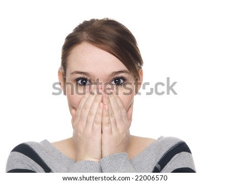 Isolate studio shot of a casually dressed young adult woman covering her mouth in surprise with eyes wide. - stock photo