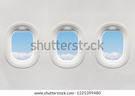 Isolated airplane window with blue sky from customer seat view #1225399480
