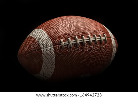 Isolated American football ball on high contrast black background
