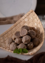 Isolated bakso or Indonesian met ball on traditional bamboo rack. Preparation for making bakso, or clear met balls soup. Selective Focus.