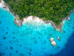 Isolated beautiful tropical island with white sand beach and blue clear water and granite stones. Top view, speedboats above coral reef. Similan Islands, Thailand.