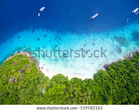 Isolated beautiful tropical island with white sand beach and blue clear water and granite stones. Top view, speedboats above coral reef. Similan Islands, Thailand. #519582163