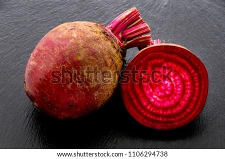 Isolated beet. Whole red beetroot and a half isolated on stone plate