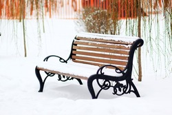Isolated bench in the park covered with snow